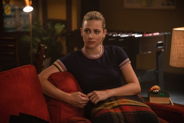 Betty sitting on a couch in Riverdale looking worried