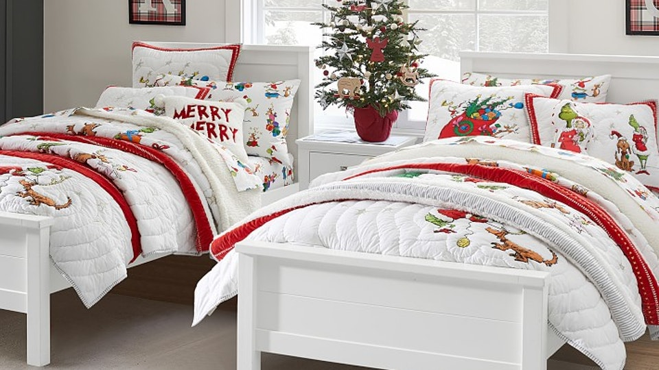 Two twin beds bedecked in white quilts with Grinch appliques