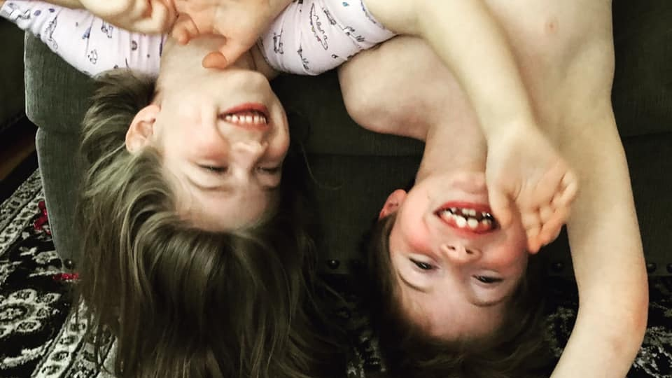 A picture of the author's children, smiling and hanging upside down from their couch.