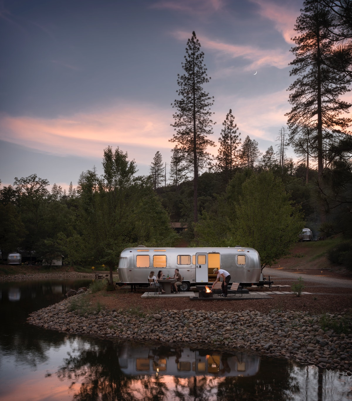 A group of friends hangs out near an AutoCamp airstream trailer at sunset.