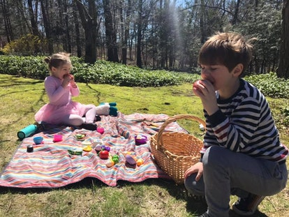 Two children enjoying a picnic outside.