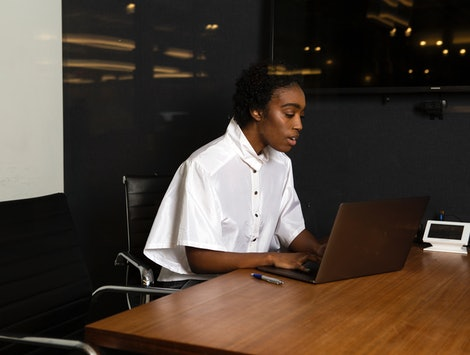 A non-binary person using a laptop at work. Millennials Being Less Healthy Than Gen Xers Comes With An Economic Impact