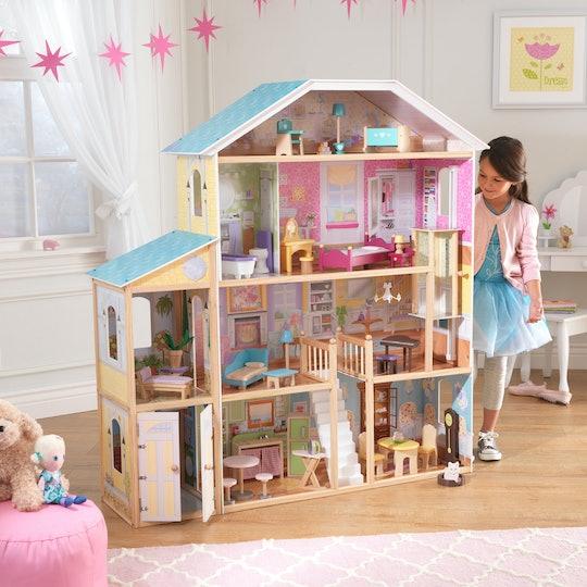 Little girl standing next to KidKraft Majestic Mansion Dollhouse