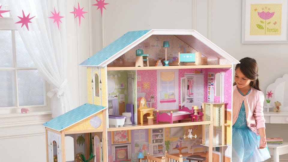Little girl standing next to KidKraft Majestic Mansion Dollhouse
