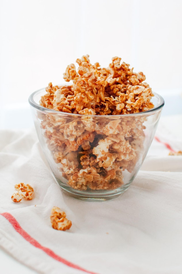 Thanksgiving sheet pan desserts, clear bowl filled with cinnamon maple caramel popcorn on a white dish towel