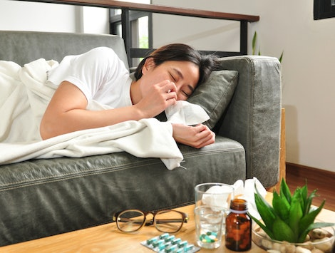 A woman with the flu lies on the couch.Vitamin c works to prevent the flu in a variety of ways.