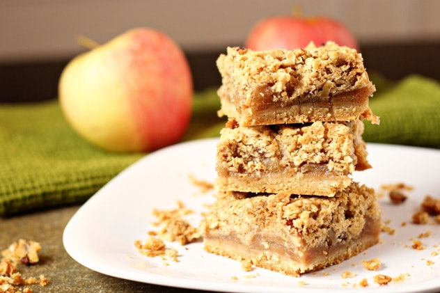 Thanksgiving sheet pan desserts, a white plate with three apple pie bars tacked on each other with crumbles around