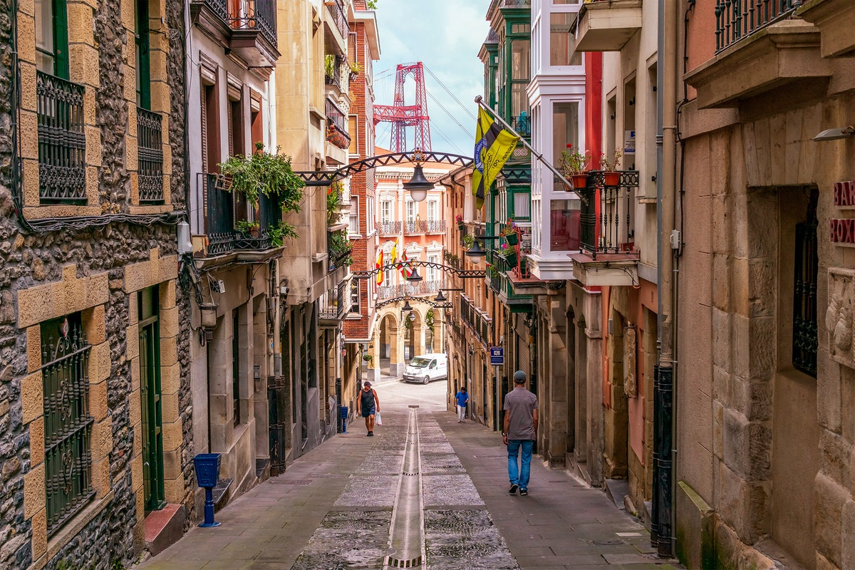 A street in Bilbao, Spain has colorful building and archways, and a view of a red bridge.