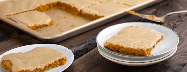 Thanksgiving sheet pan desserts, pumpkin sheet cake with brown sugar icing, cut into squares on sheet pan, two squares on white plates next to the pan