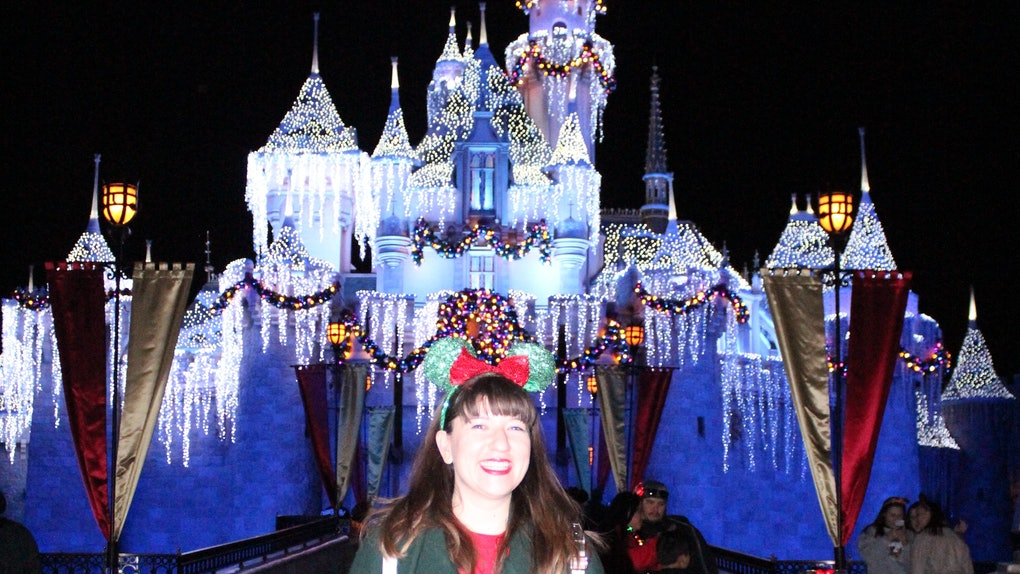A smiling woman wearing festive Minnie ears stands in front of Disneyland's castle during the holidays.