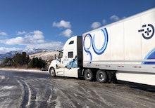 An autonomous semi truck driving through sleet.