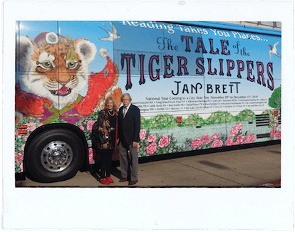 Jan Brett and her husband Joe Hearne stand in front of their tour bus