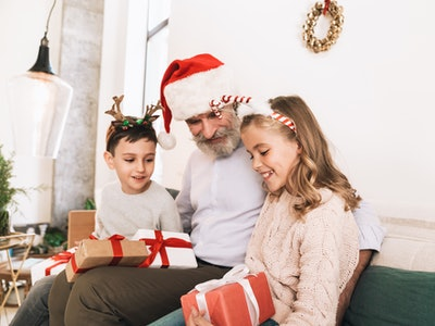 best holiday gifts for grandparents; grandpa opening christmas gifts with his grandkids