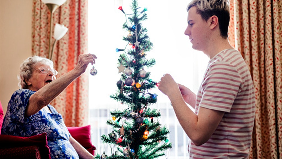 kid helping a elderly woman decorate christmas tree in a nursing home