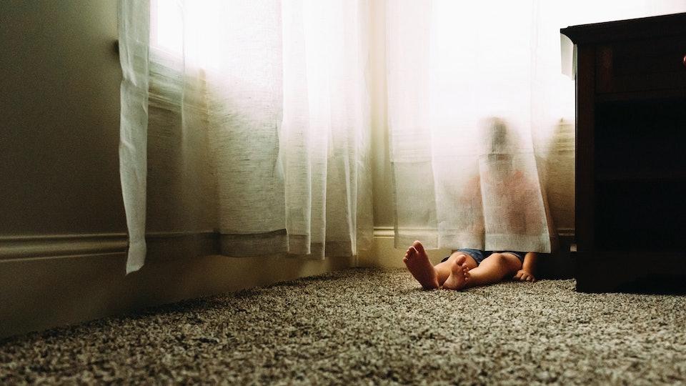 Child hides behind a curtain