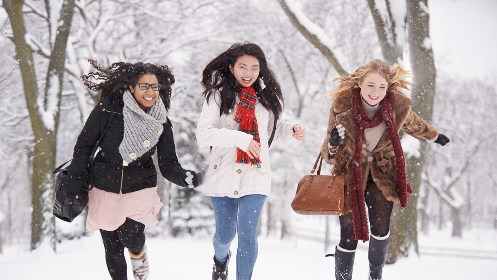 Three girl friends running in snow during Winter Solstice 2019