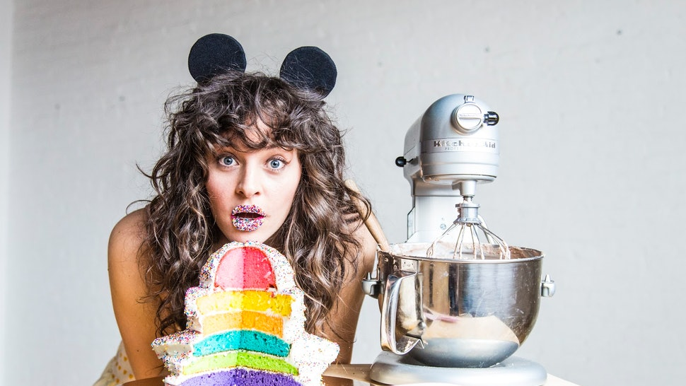 Amirah Kassem of Flour Shop poses with one of her signature rainbow cakes and a kitchenaid mixer.