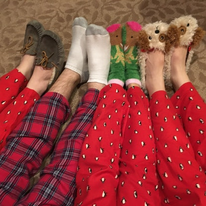 A family all in Christmas pajamas puts out their legs