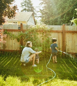 A mom waters the garden with her son