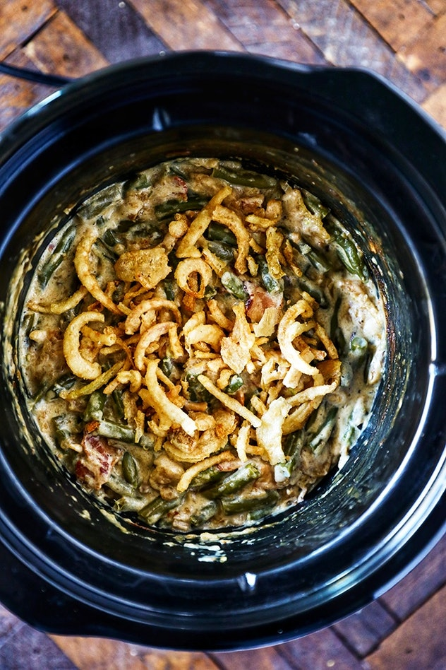 Crock pot full of green bean casserole with fried onions on top