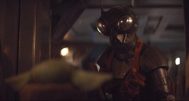 The droid Zero approaches Baby Yoda in The Mandalorian