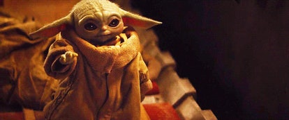 Baby Yoda looks at his hand after trying to use the Force in The Mandalorian