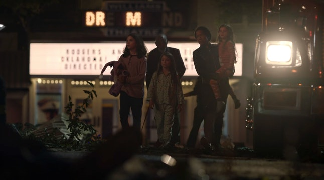 The Abar family walking in front of the Dr. M lights in the Dreamland Theater in Watchmen