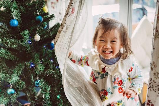 little girl hides behind curtains near Christmas tree