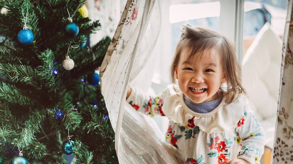 little girl hides behind curtains near Christmas tree