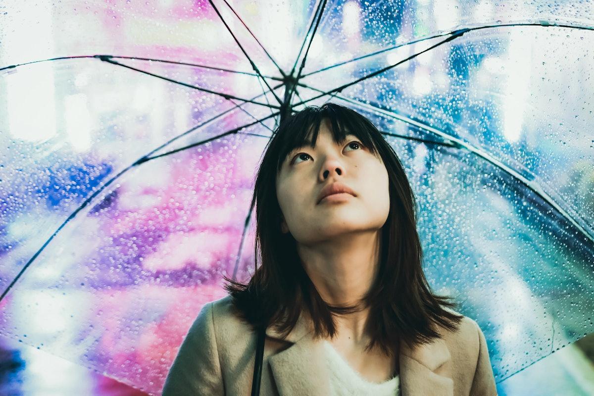Young Asian woman in the rain during Capricorn season 2019.
