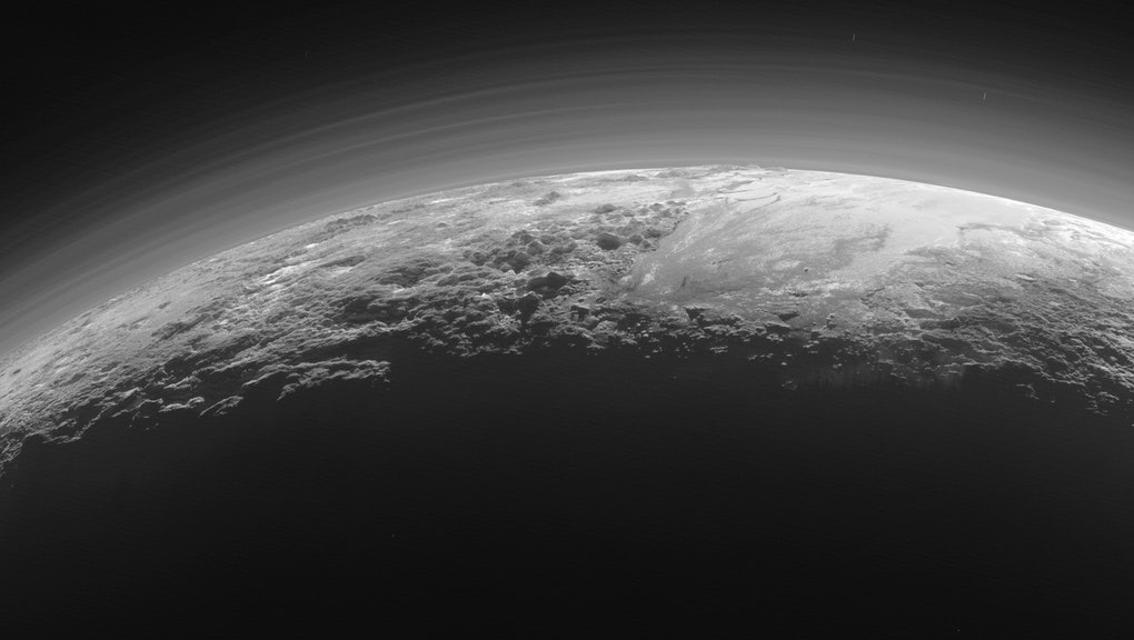 In 2015, NASA's New Horizons spacecraft looked back toward the sun and captured this near-sunset view of the rugged, icy mountains and flat ice plains extending to Pluto's horizon.