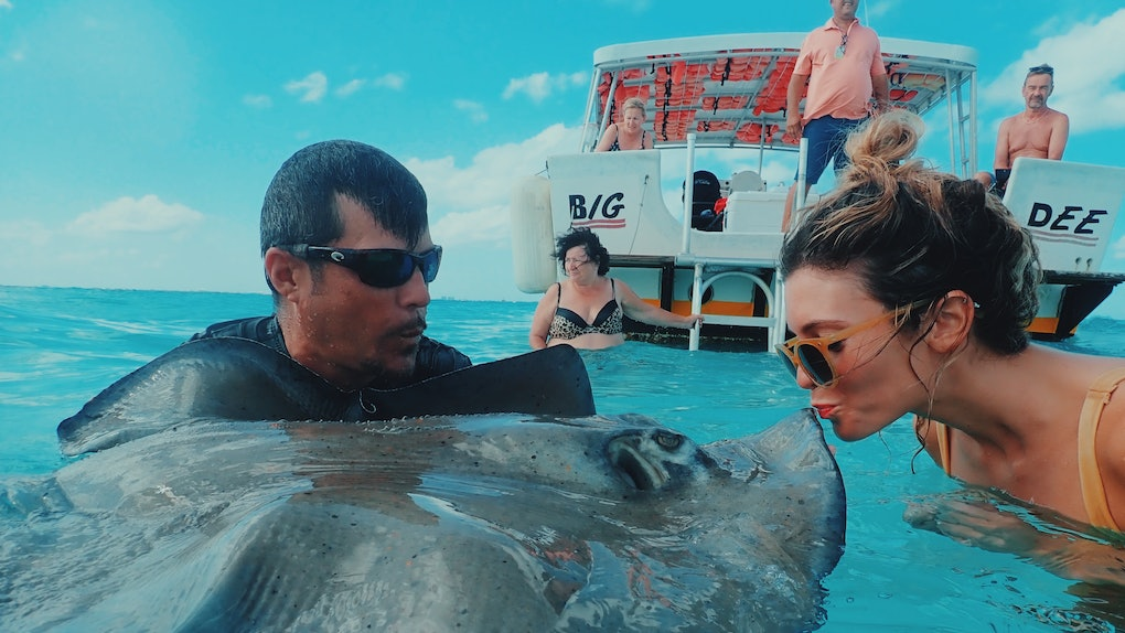 A girl in sunglasses and a bikini kisses a stingray in the water.