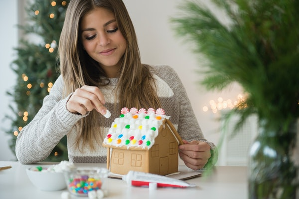 Young woman building gingerbread house.