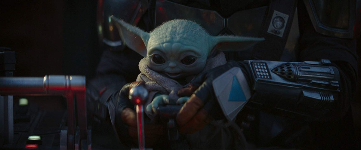 Baby Yoda happily looks at the buttons and switches of a spacecraft in 'The Mandalorian.'