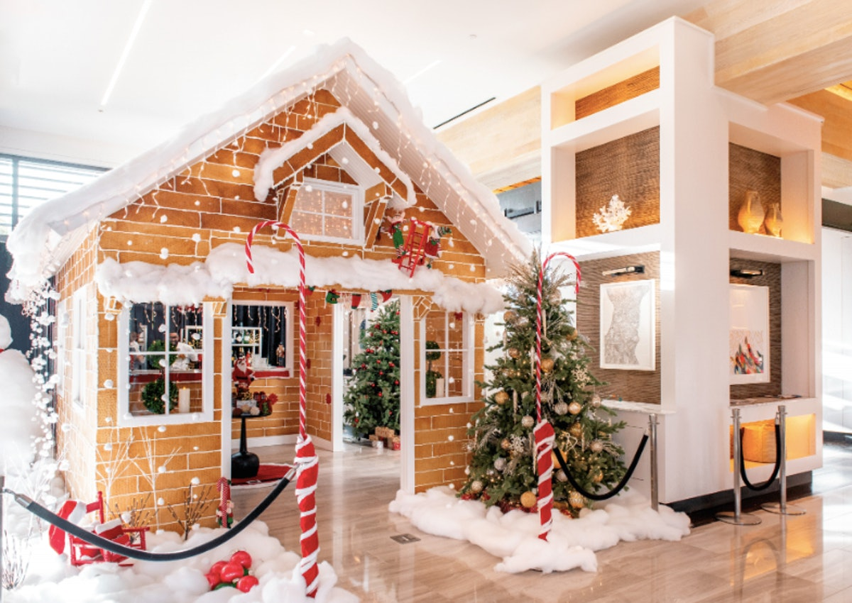 A life-size gingerbread cocktail bar is surrounded by fake snow, Christmas trees, and festive decor ...
