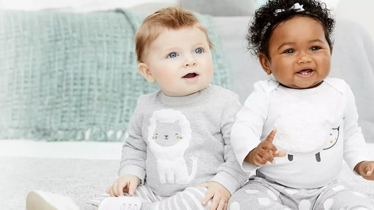 Two babies sitting next to each other in grey outfits as part of a Carter's sale ad