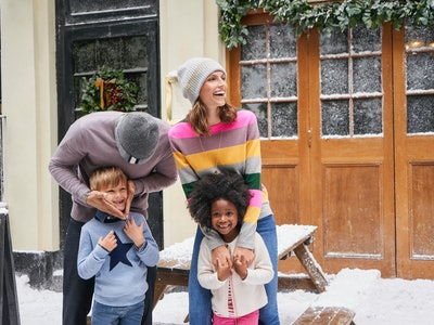 a man, woman, boy and girl wearing clothes from boden's holiday sale outside in the snow
