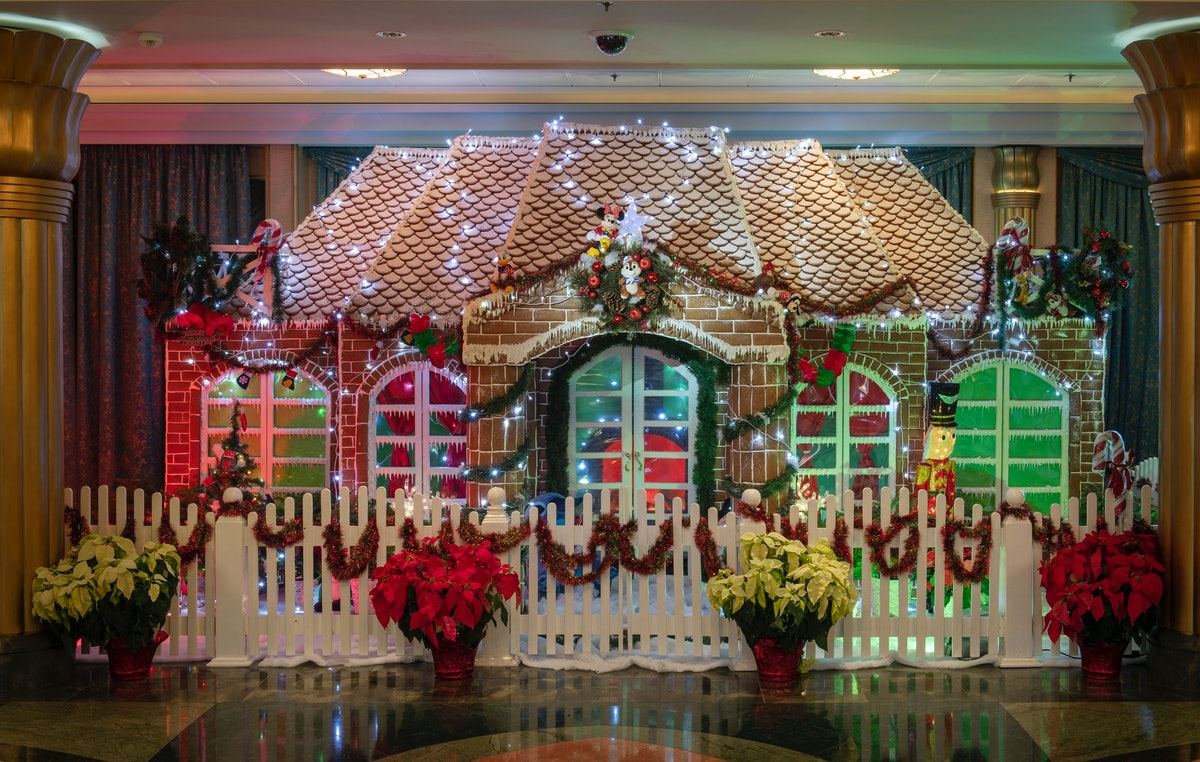 A giant gingerbread house with poinsettias surrounding it is on display on the Disney Cruise Line du...