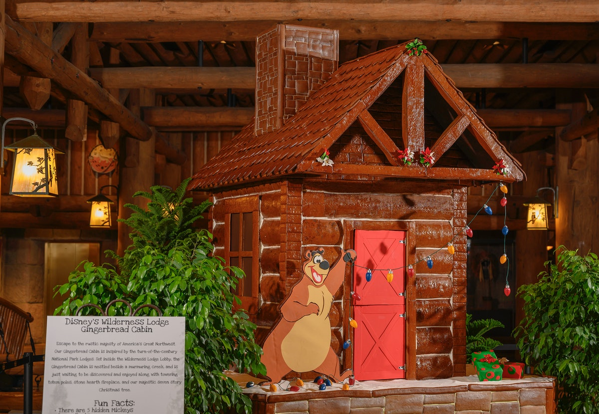 A gingerbread log cabin with a bear hanging Christmas lights is on display at Disney's Wilderness Lo...