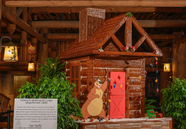 A gingerbread log cabin with a bear hanging Christmas lights is on display at Disney's Wilderness Lodge during the 2019 holiday season.