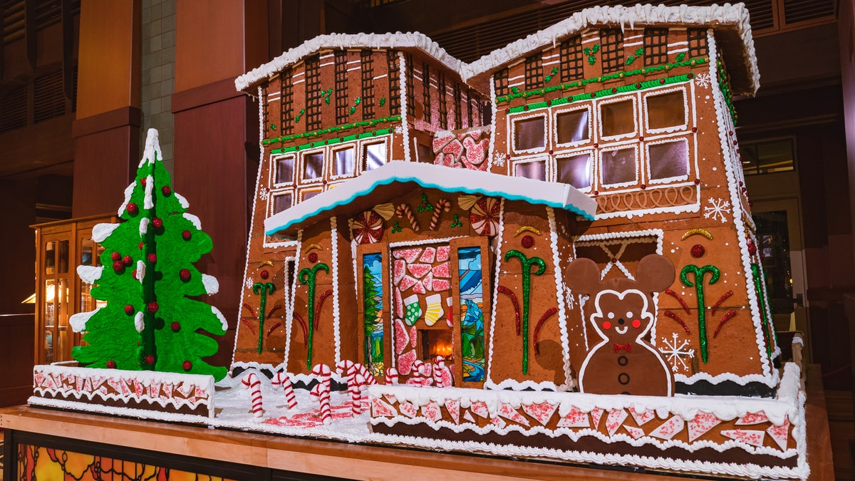 A giant gingerbread house with a Mickey gingerbread and Christmas tree in front is on display at Dis...