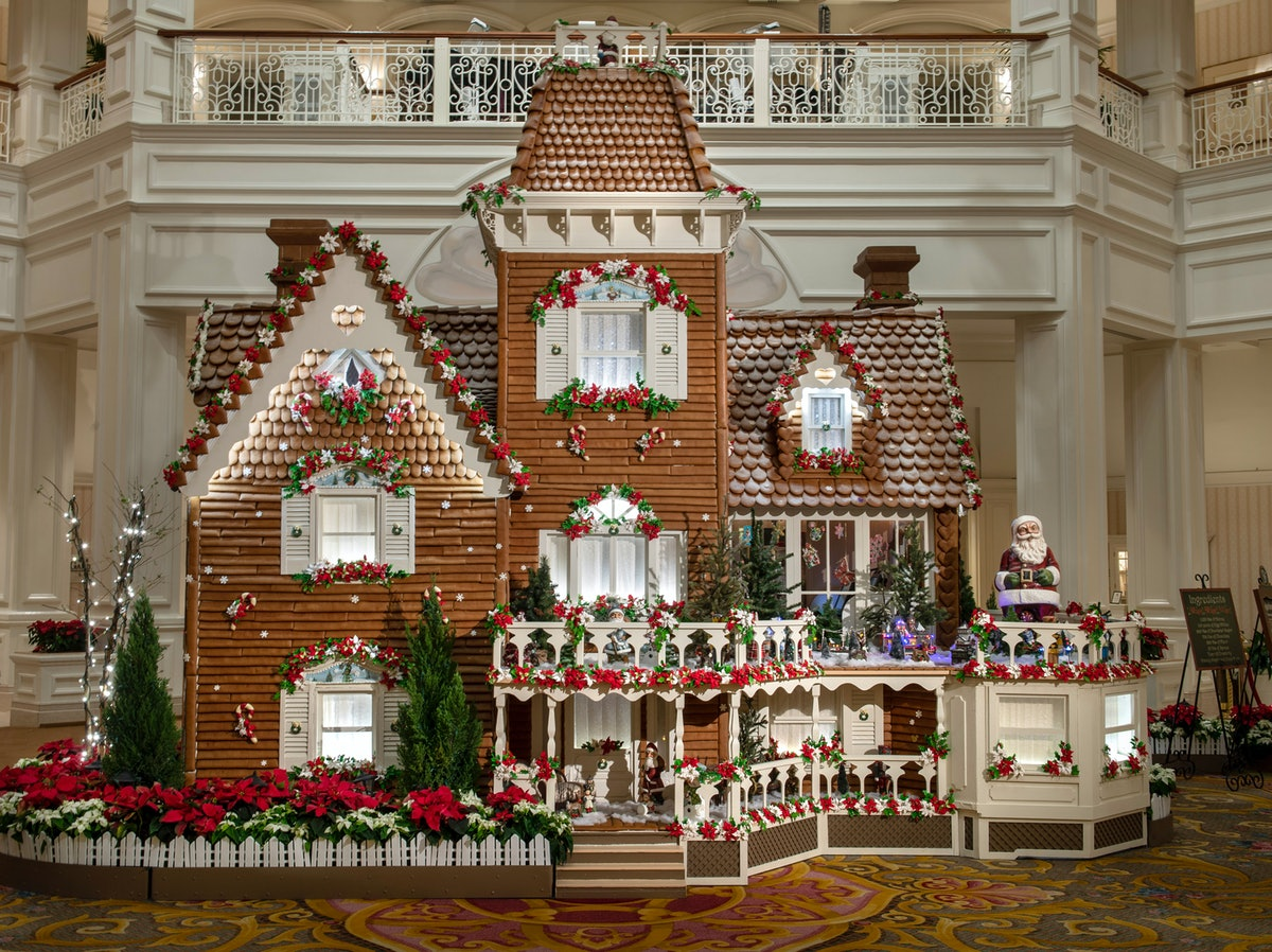 The giant gingerbread house decorated with poinsettia plans sits in the lobby of the Grand Floridian...