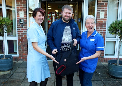 A Disney representative shows the laptop containing the final Star Wars film to Rowans Hospice Healthcare Support Worker Lisa Davies (left) and Senior Staff Nurse Jill Saunders (right).