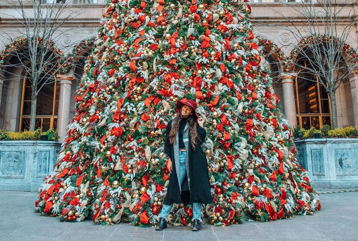 A travel blogger poses in front of the Christmas tree at Lotte New York Palace in a wintertime outfit.