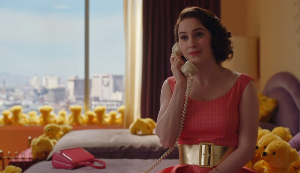 """A scene from 'The Marvelous Mrs. Maisel"""" where Midge sits on a bed in a pink dress and is surrounded..."""