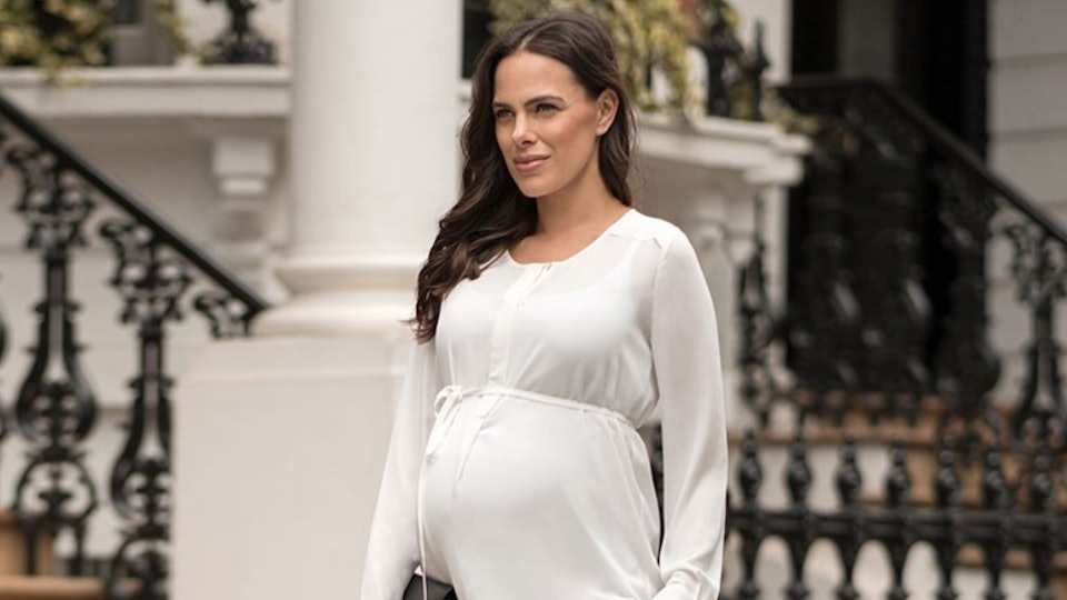 Image of a pregnant woman in a white maternity top and black pants walking outside