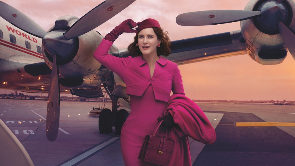 'The Marvelous Mrs. Maisel' Rachel Brosnahan stands on an airplane runway dressed in pink.