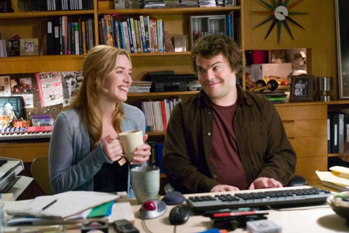 Jack Black and Kate Winslet smile sit in front of a piano with mugs of tea and laugh in a scene from...