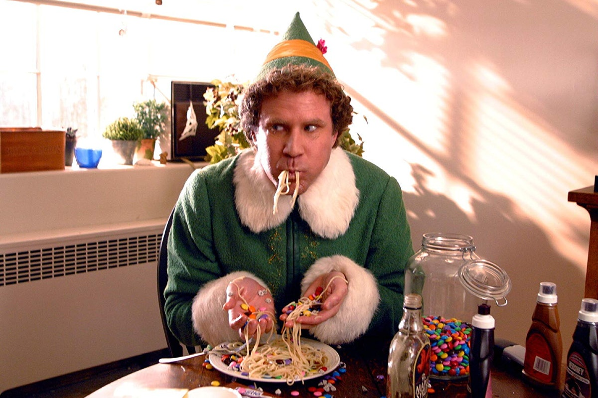 Buddy the Elf eats spaghetti and candy at a kitchen table in the Christmas movie, 'Elf.'
