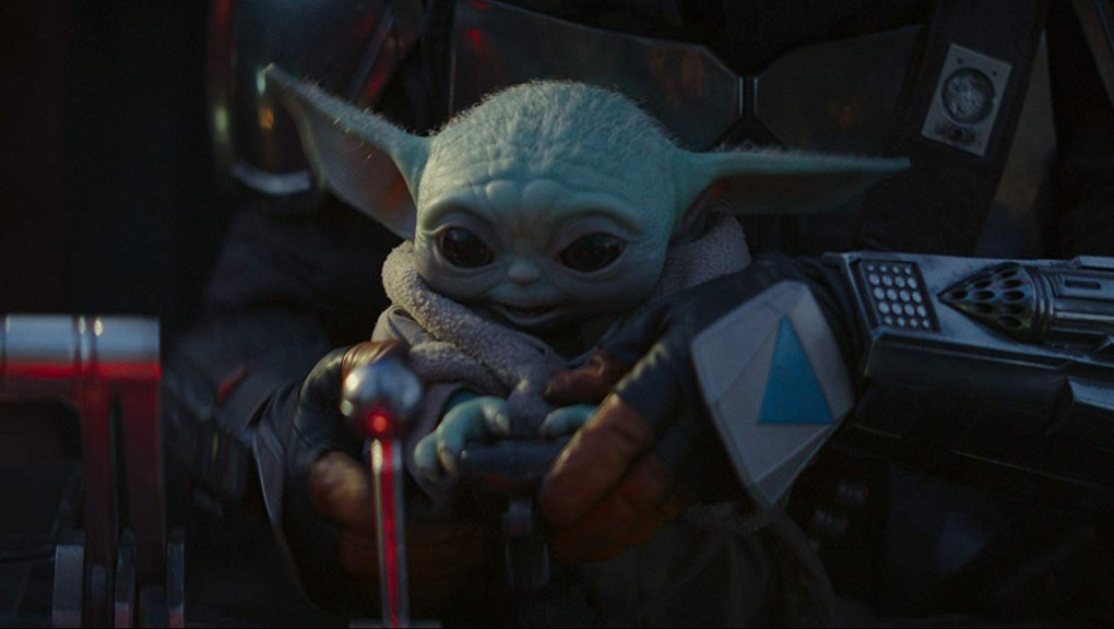 The Mandalorian is holding Baby Yoda, who is smiling and reaching for something.